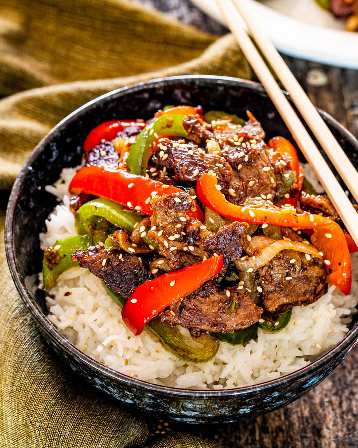 asian pepper steak over a bed of rice in a bowl.