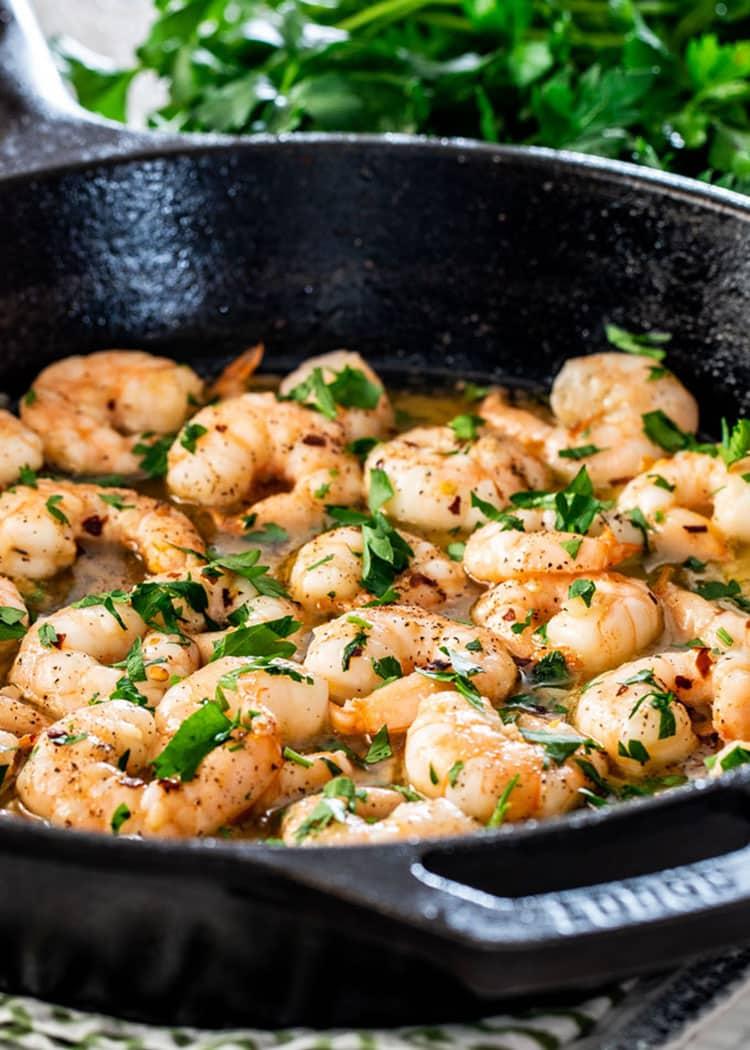 garlic butter shrimp in a black skillet garnished with fresh parsley.