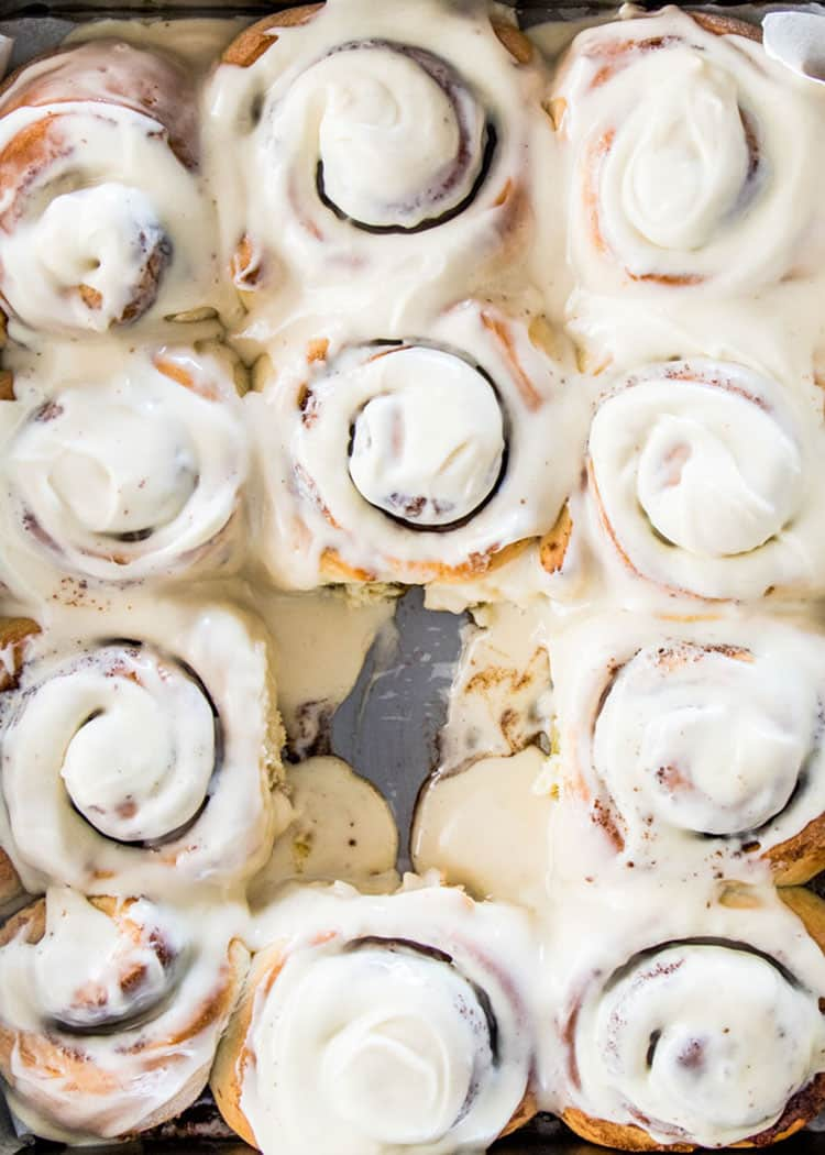 overhead shot of cinnamon rolls in a baking pan with cream cheese icing