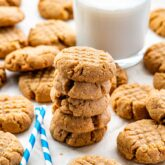 a stack of peanut butter cookies in front of a glass of cold milk.