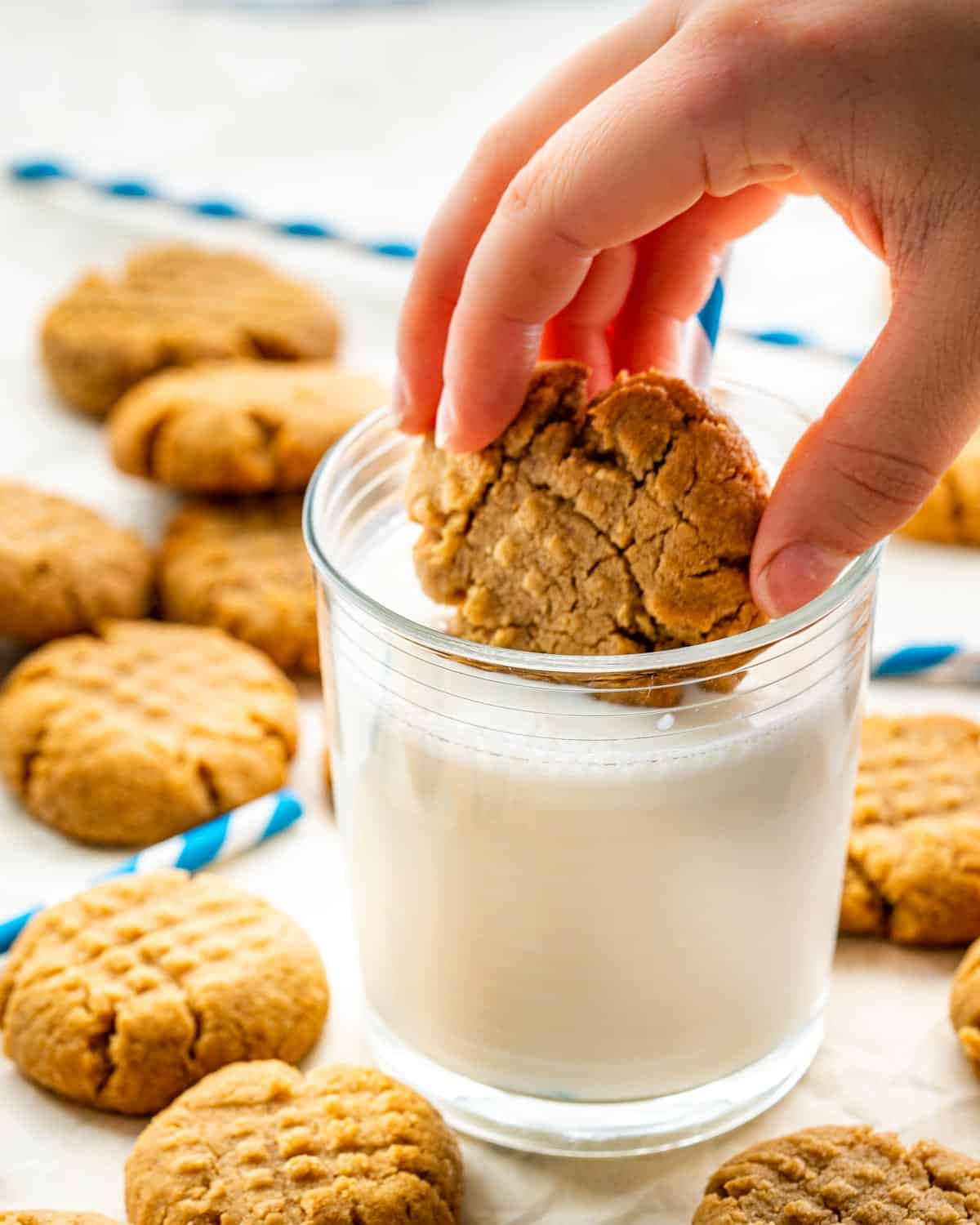 a hand dunking a peanut butter cookie in a glass of cold milk.