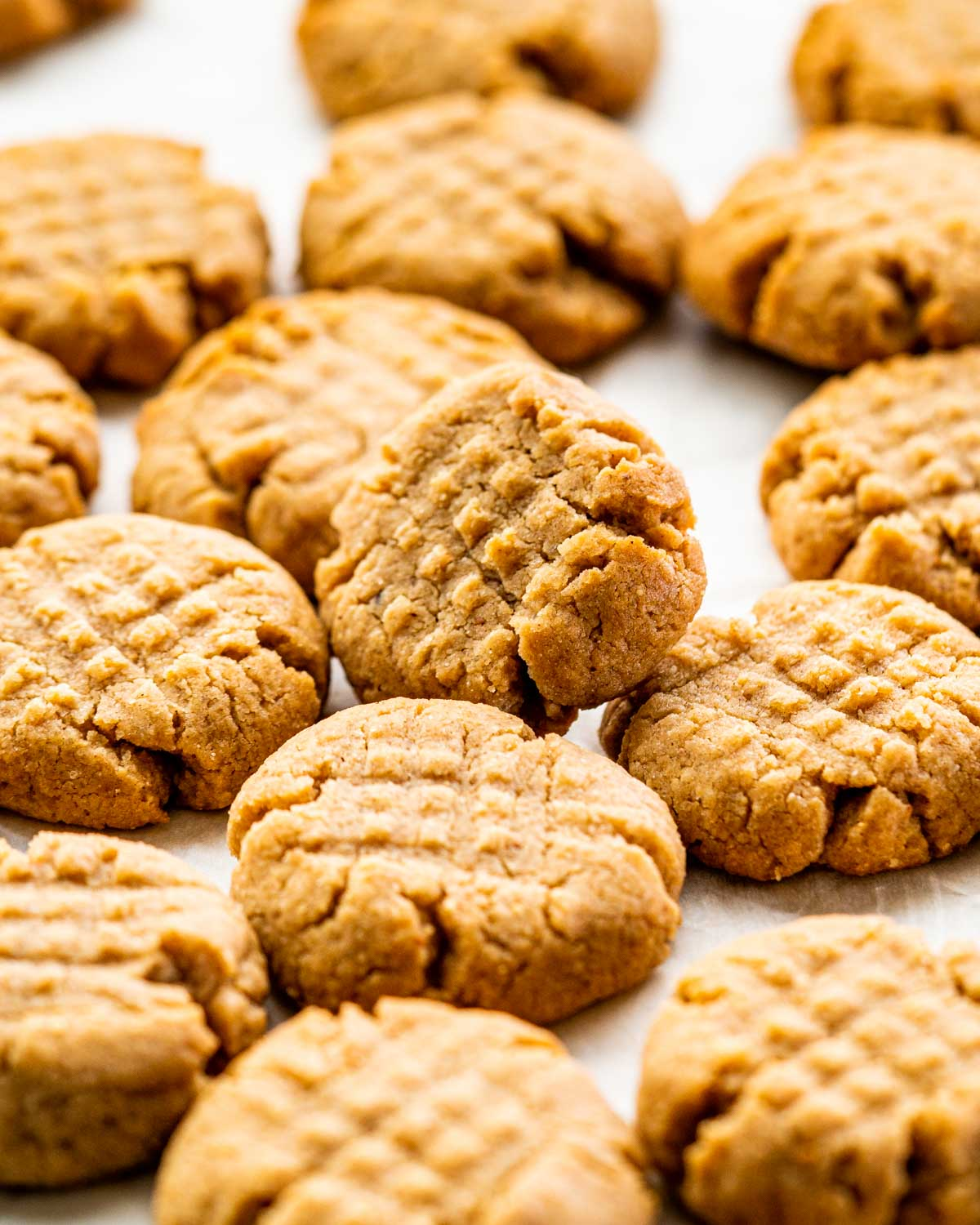 a bunch of peanut butter cookies on parchment paper.