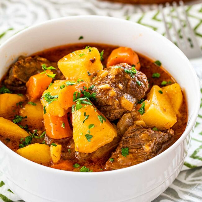 a white bowl filled with beef stew and garnished with parsley.