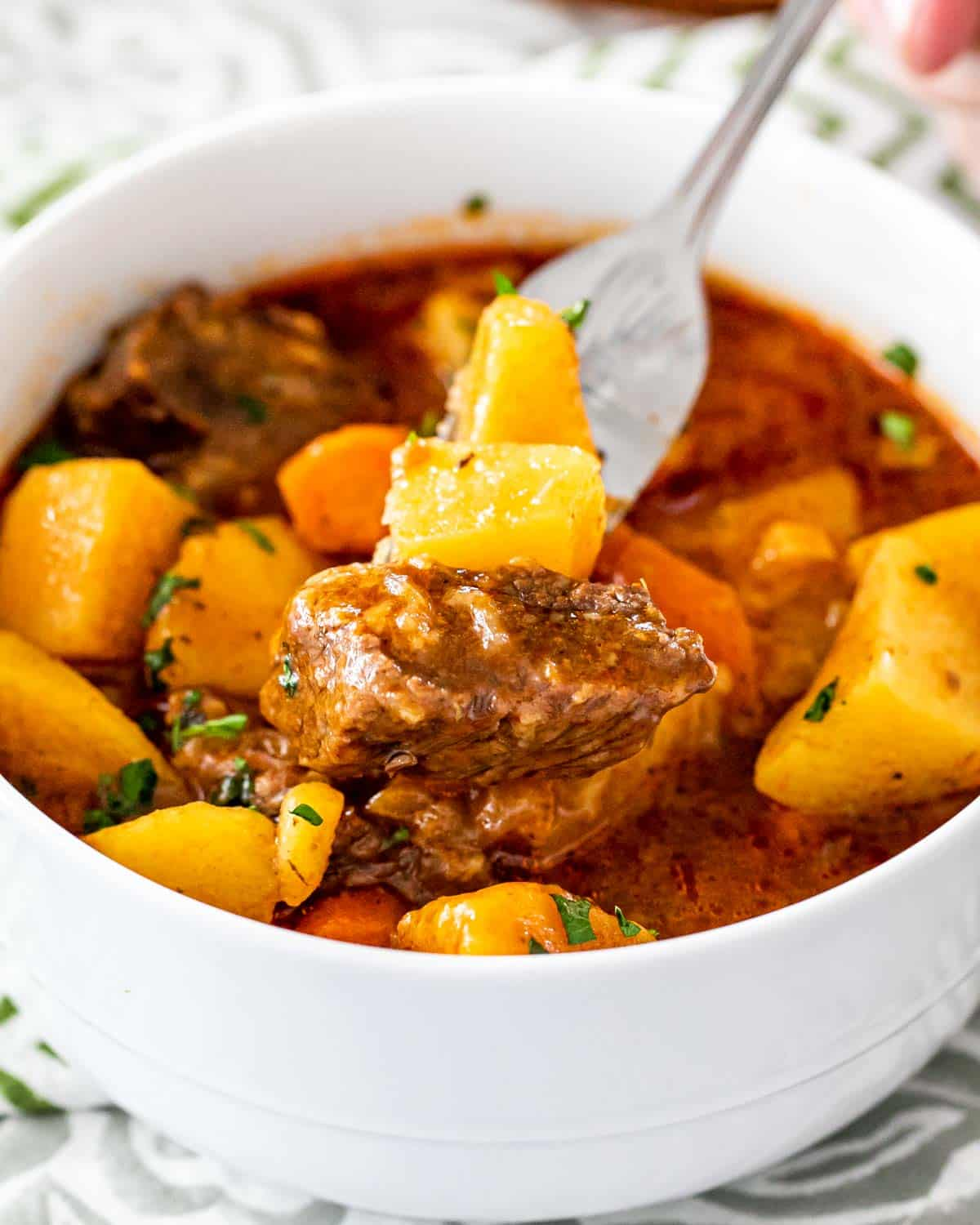 a white bowl filled with beef stew with a fork holding a piece of beef and potato.