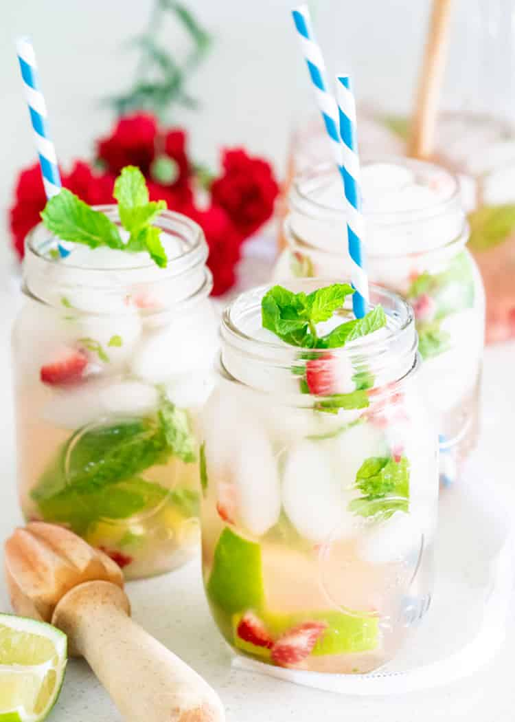 three mason jars filled with mojito with blue straws