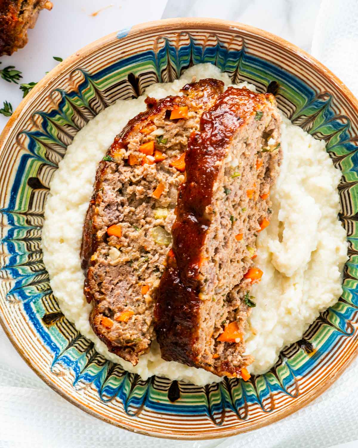 two slices of meatloaf over a bed of mashed cauliflower.