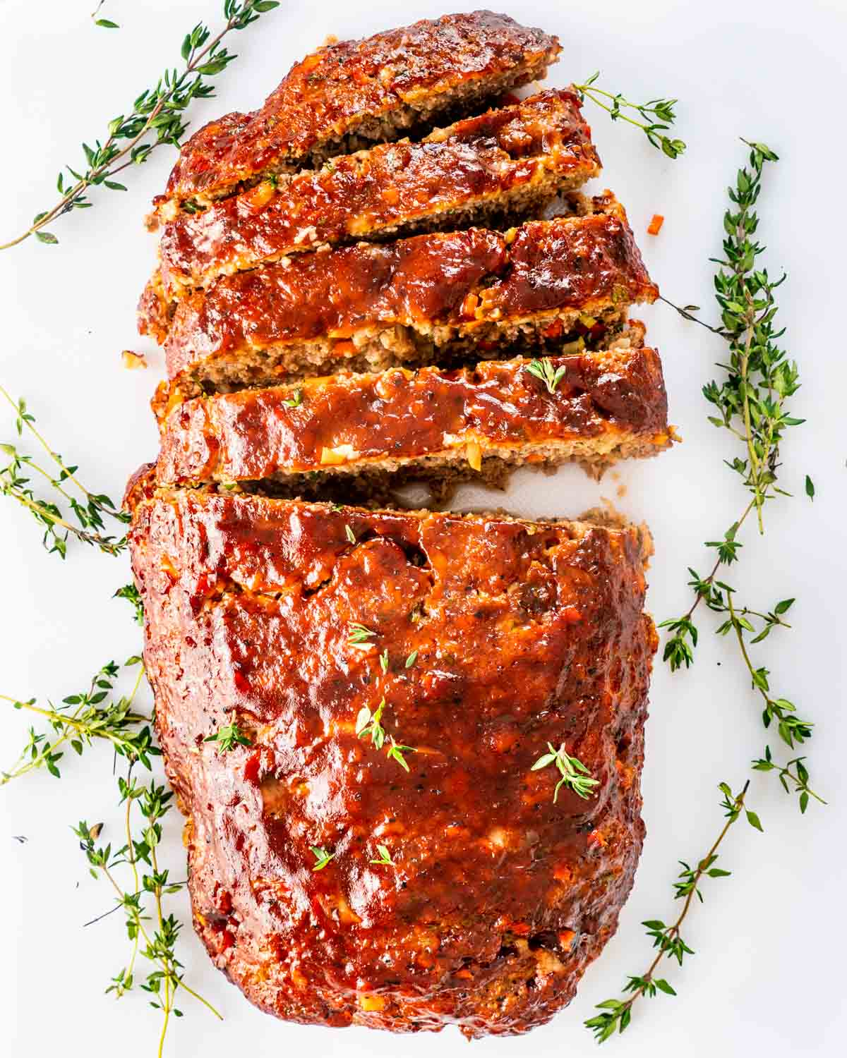 overhead shot of a meatloaf sliced on a white cutting board.