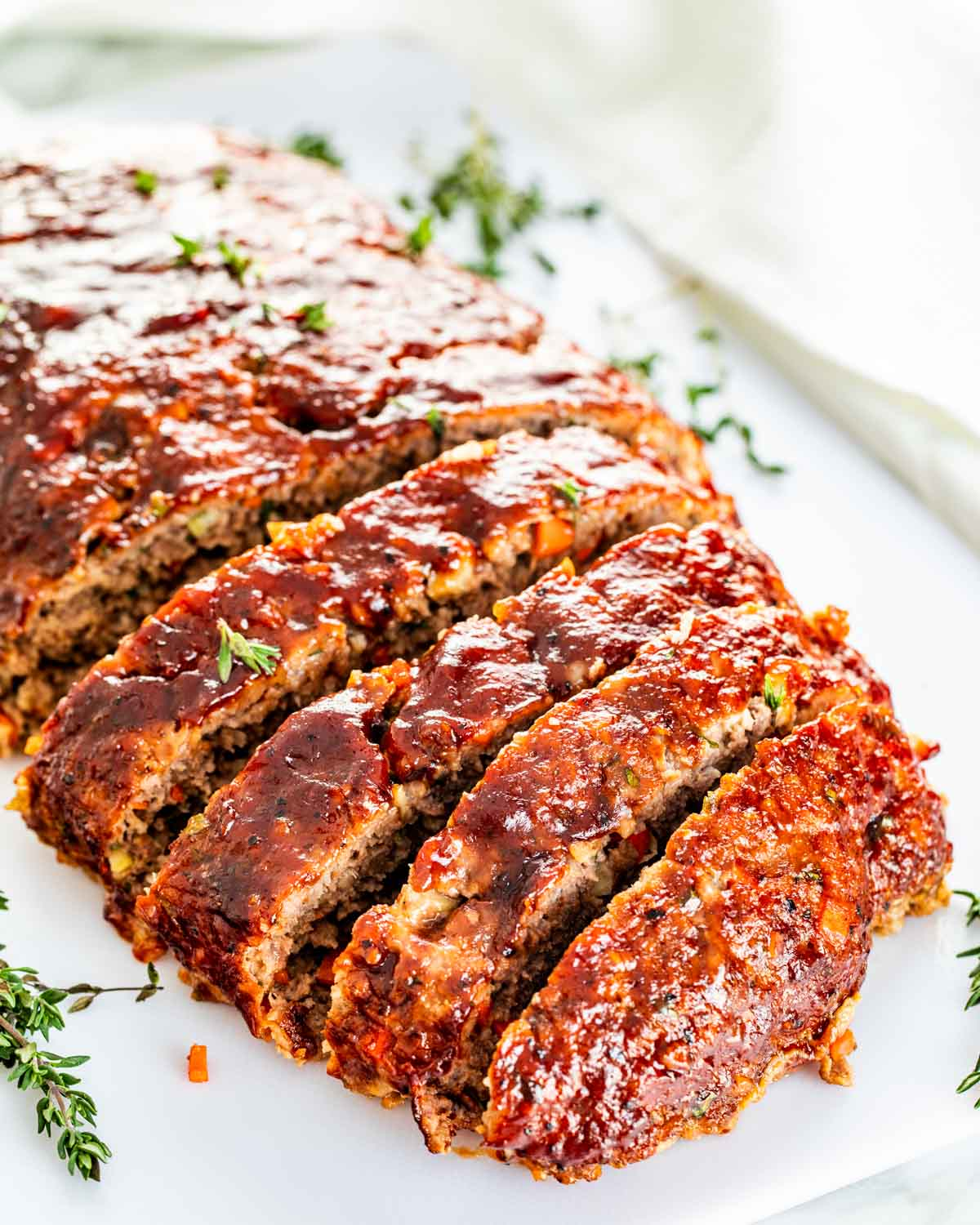 meatloaf sliced on a white cutting board.