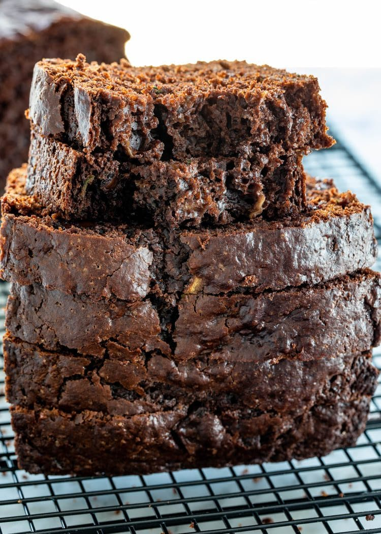 a stack of chocolate zucchini bread slices on a cooling rack
