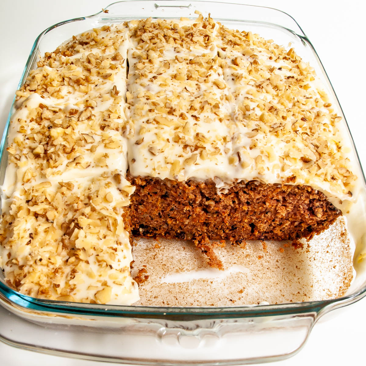carrot cake in a baking dish topped with cream cheese icing and walnuts
