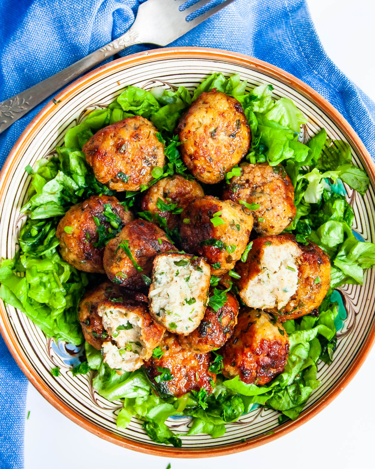 Firecracker Chicken Meatballs over a lettuce salad on a plate