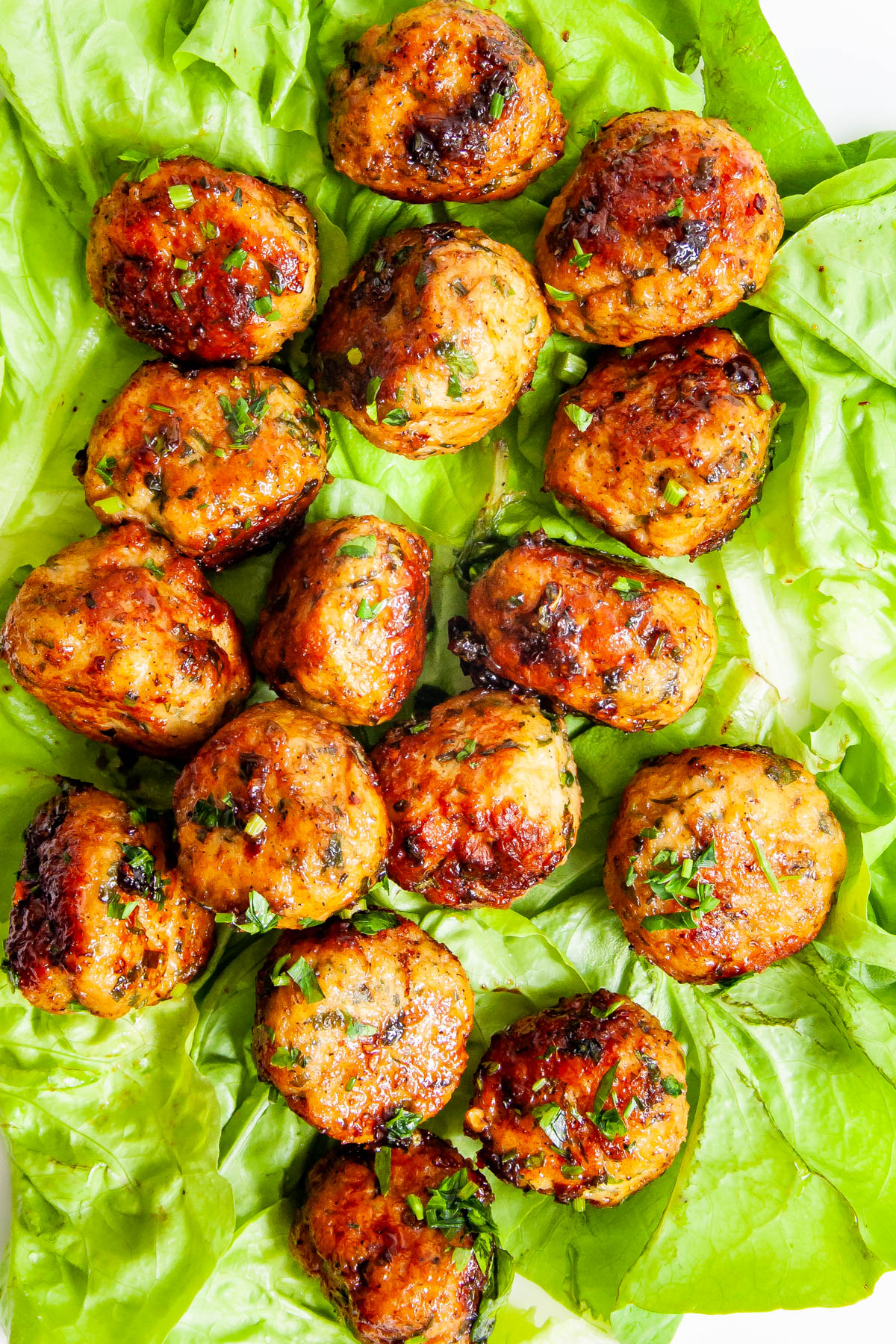 Firecracker Chicken Meatballs over lettuce leaves