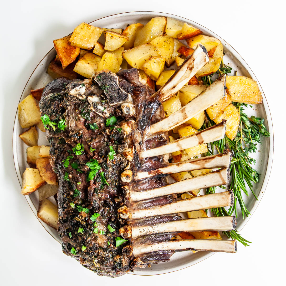 overhead shot of a rack of lamb on a white plate with roasted potatoes