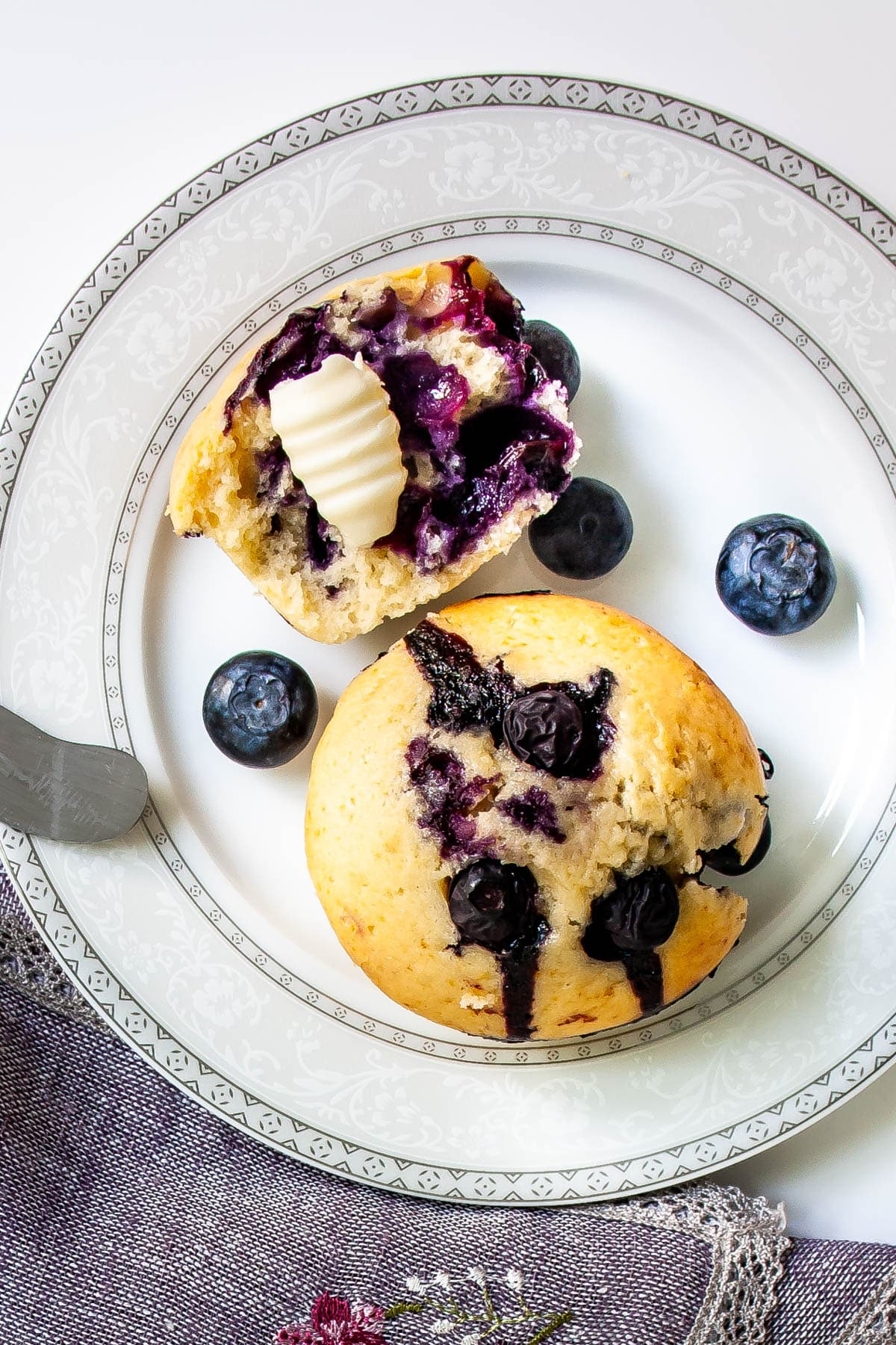 overhead shot of a white plate with a blueberry muffin and half a blueberry muffin