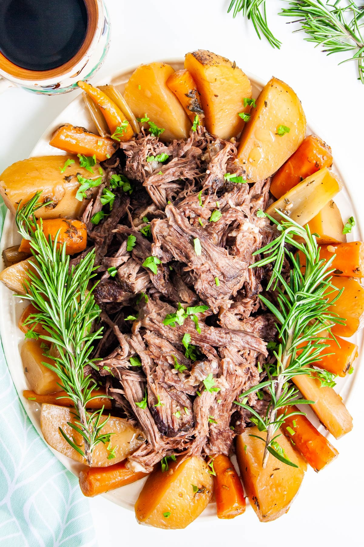 overhead shot of a platter of shredded pot roast with potatoes and carrots