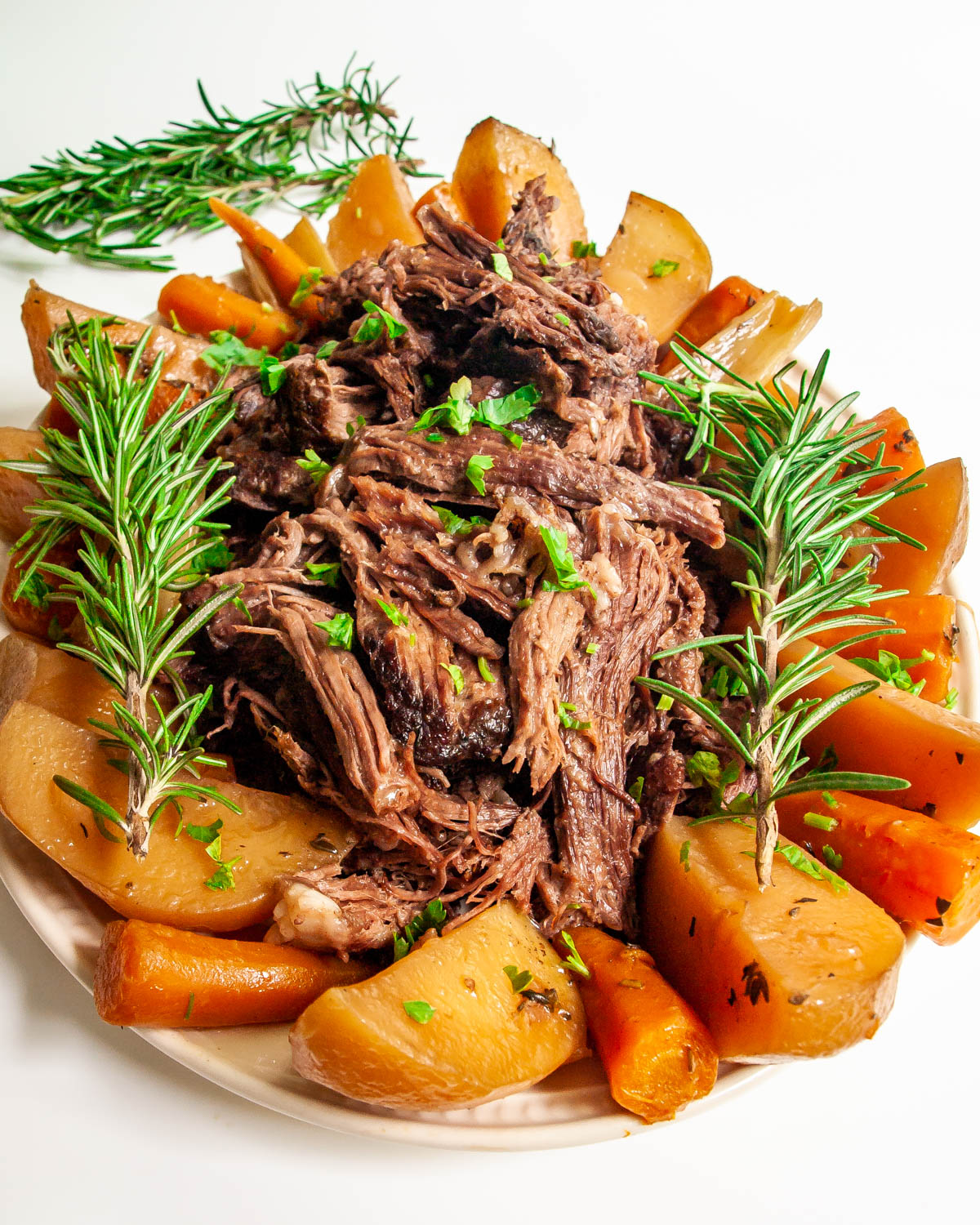 shredded roast in a platter with carrots and potatoes