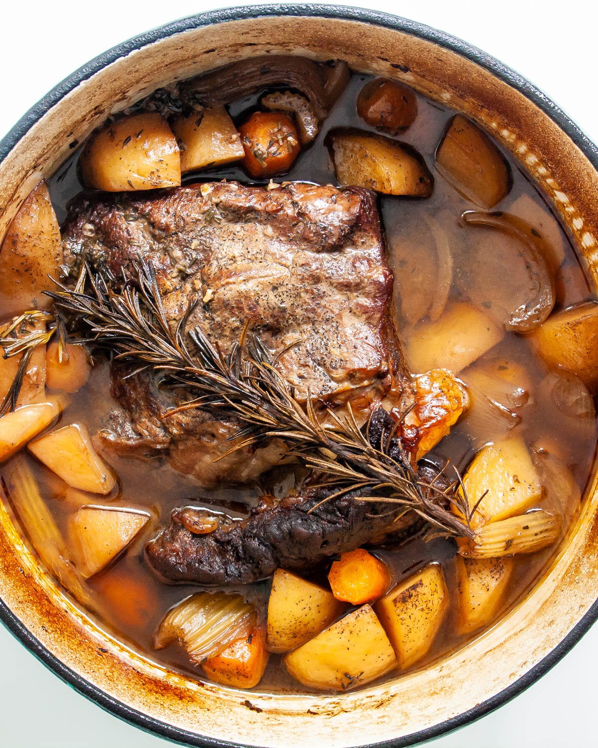 overhead of a roast in a large pot with carrots and potatoes