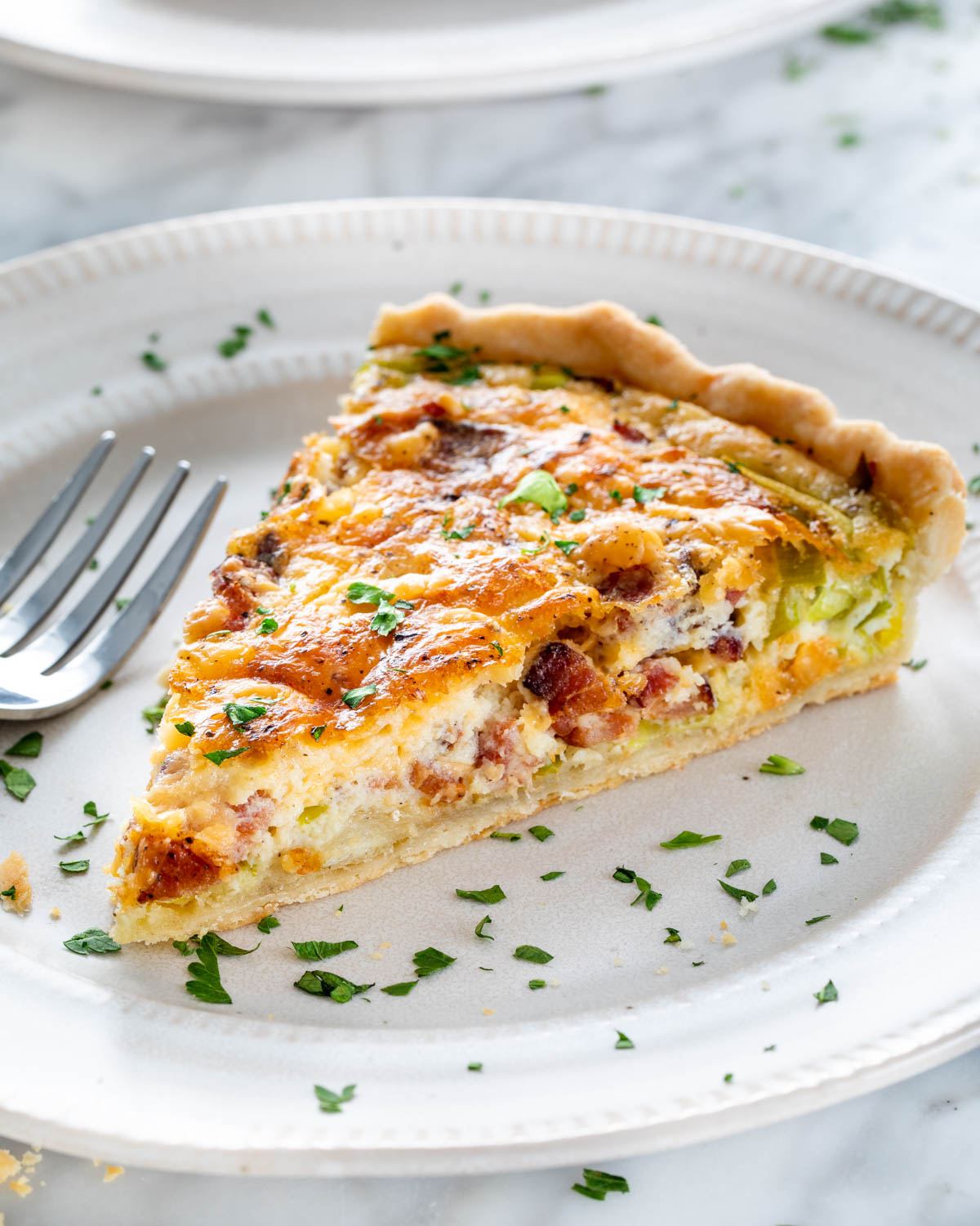 a slice of quiche on a white plate garnished with parsley