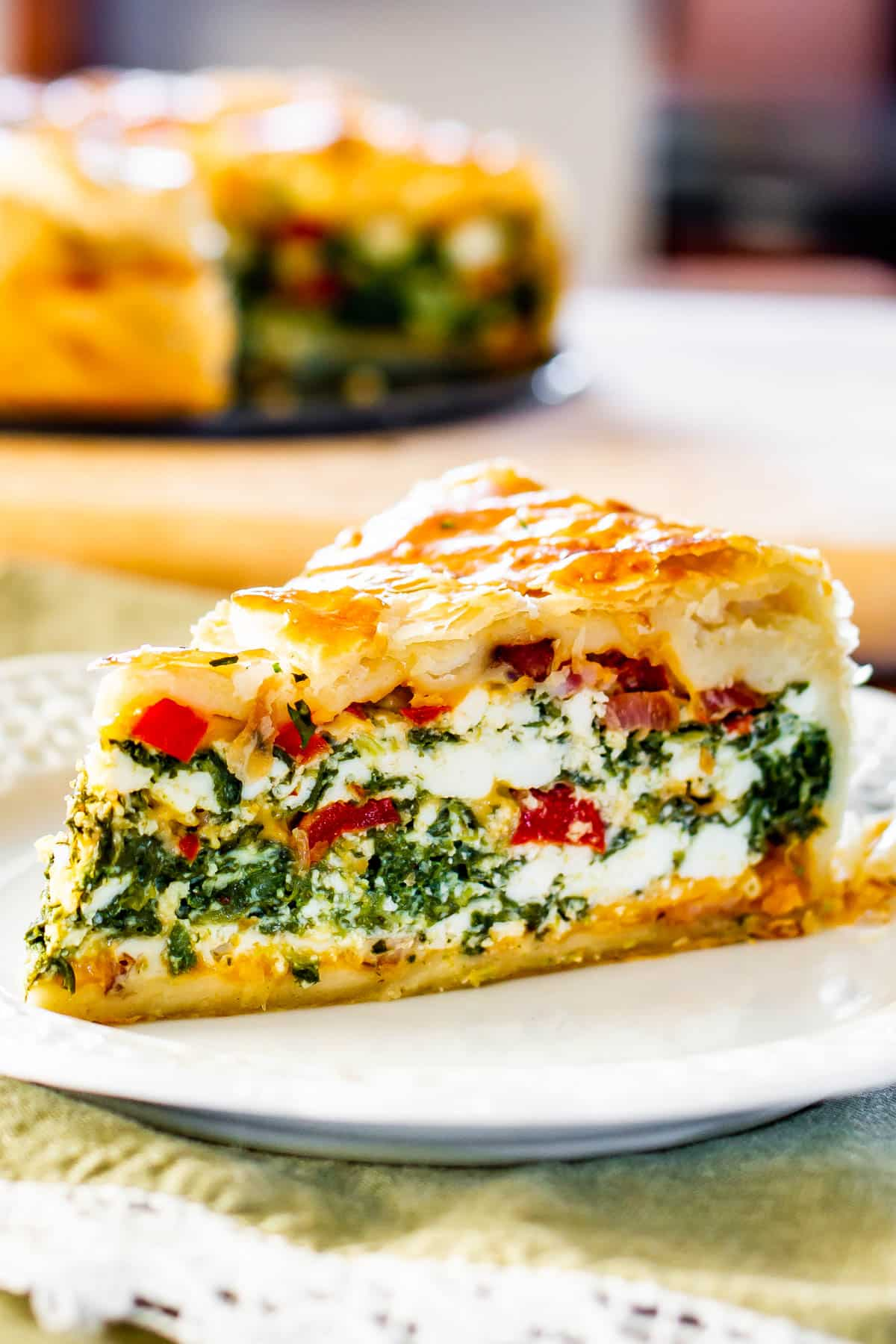 a slice of spinach ricotta brunch bake on a white plate