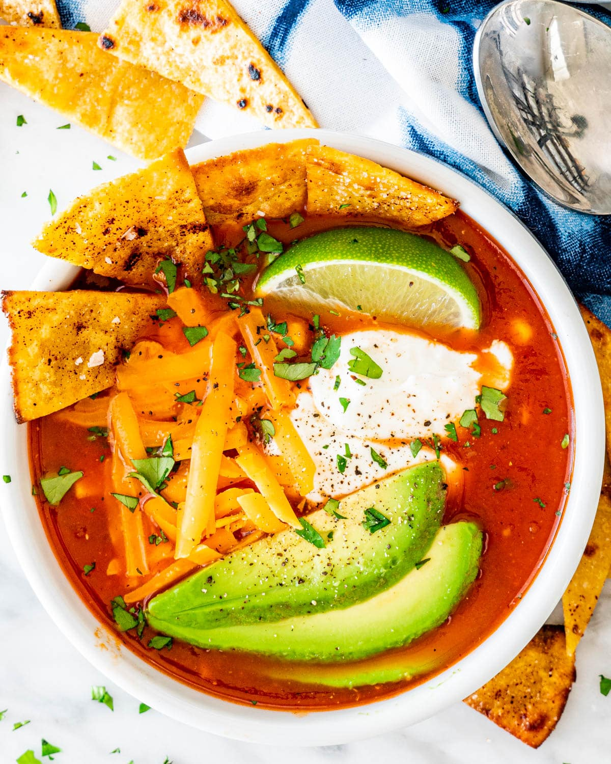 overhead shot of chicken tortilla soup in a white bowl