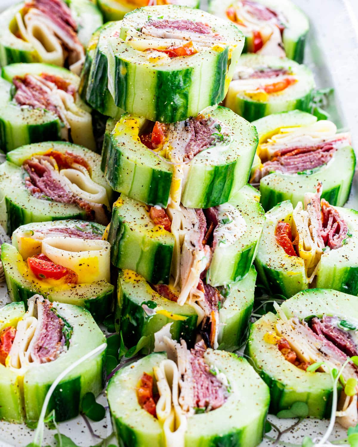 Finished cucumber sandwiches stacked on a white platter with black pepper sprinkled on top