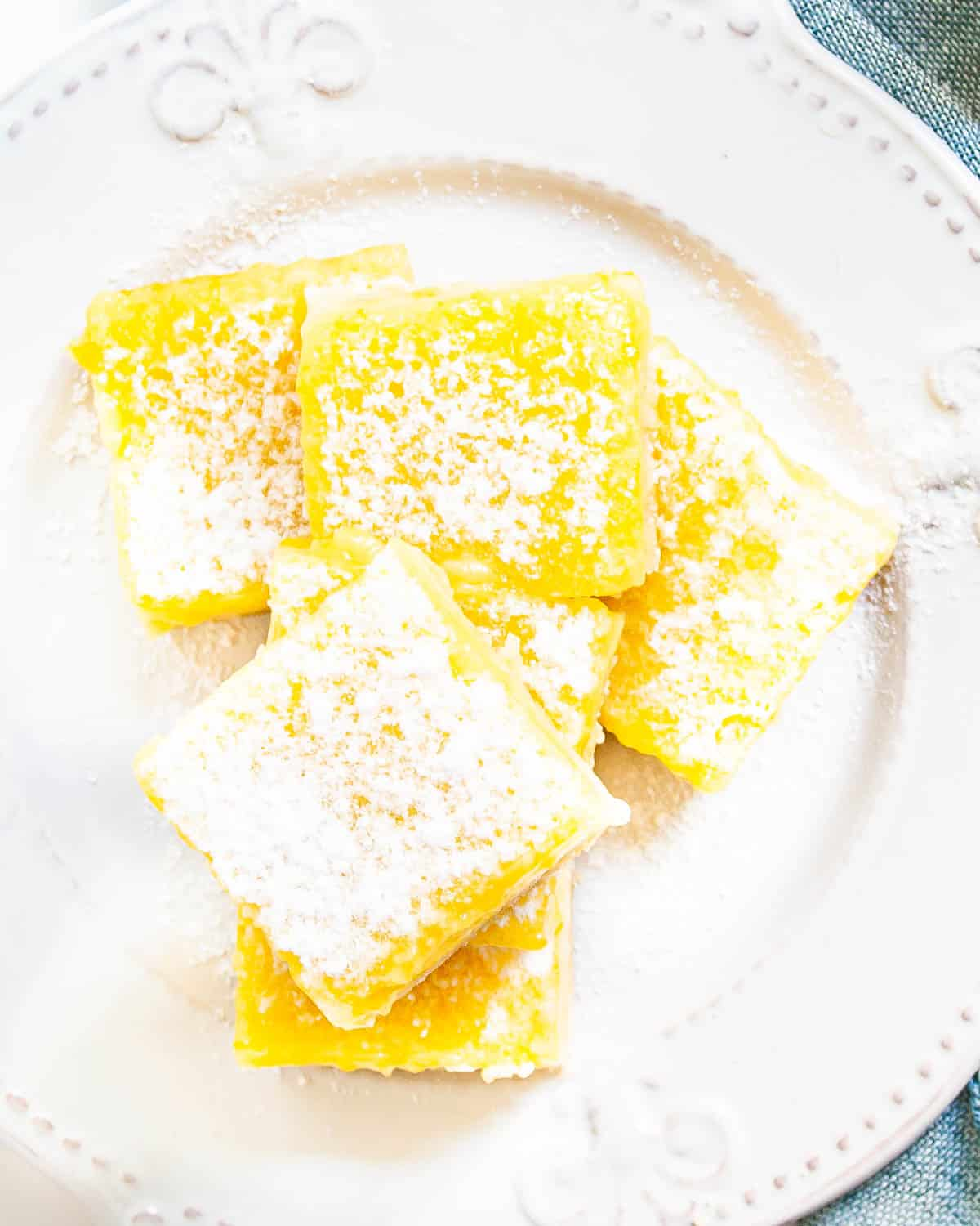overhead shot of lemon bars on a white plate dusted with powdered sugar