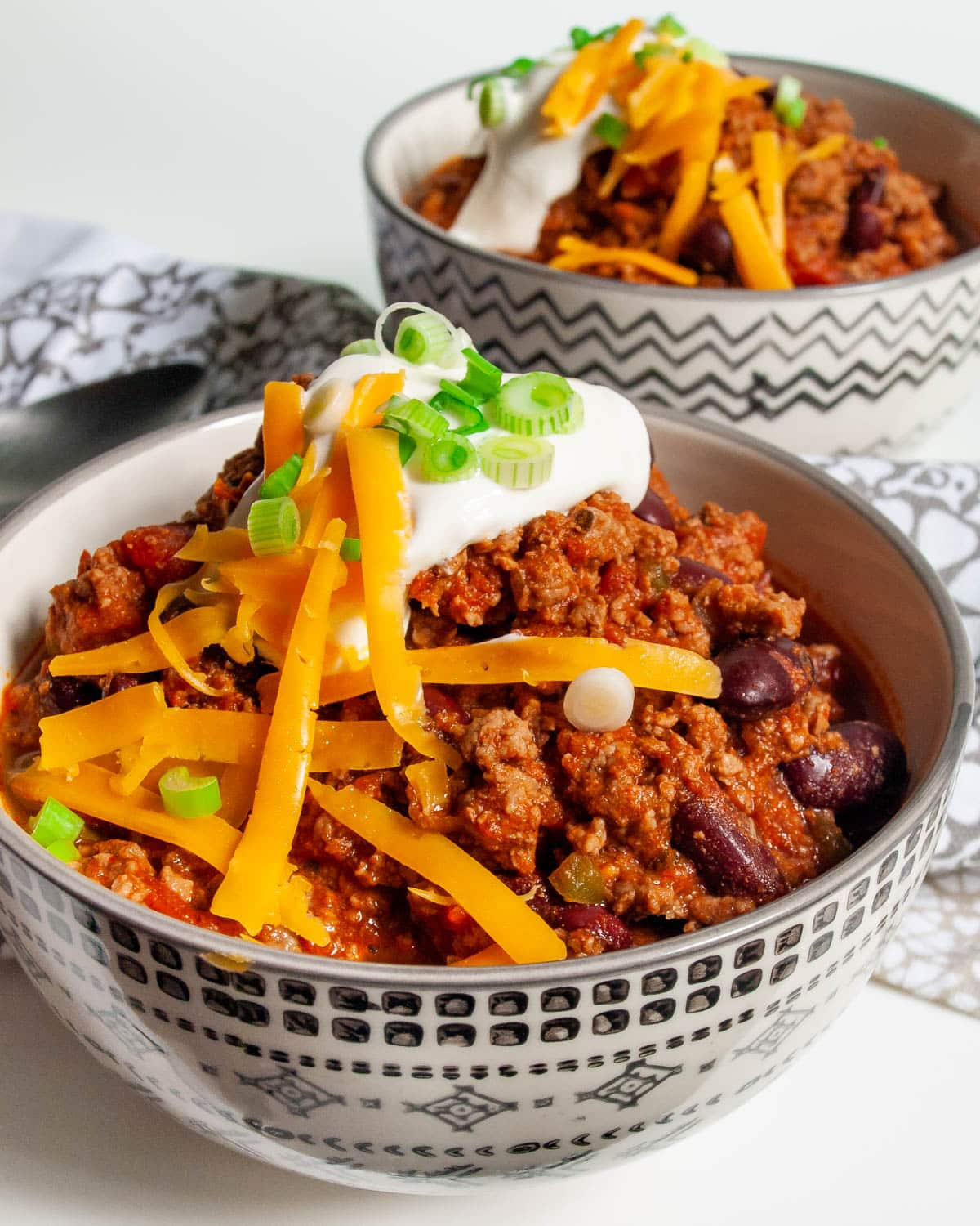 two bowls loaded with chili and topped with sour cream and cheddar cheese