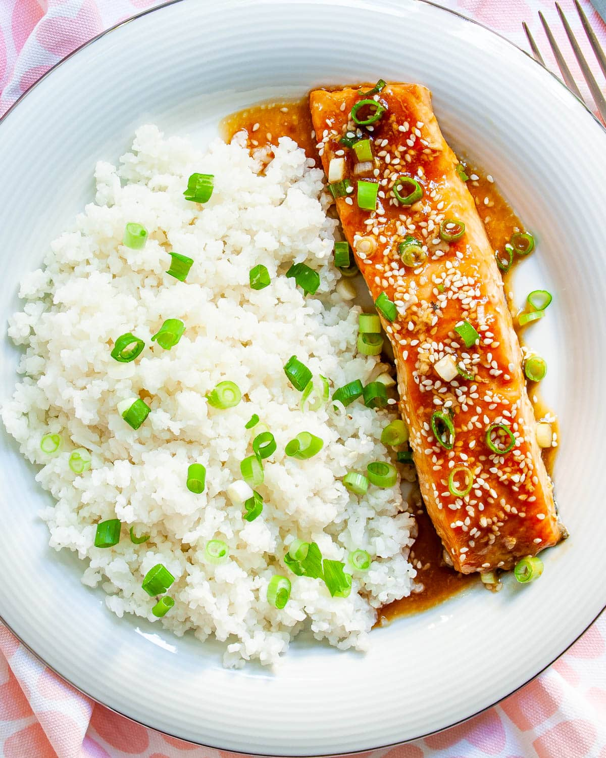 overhead shot of baked teriyaki salmon and coconut rice on a white plate garnished with green onions