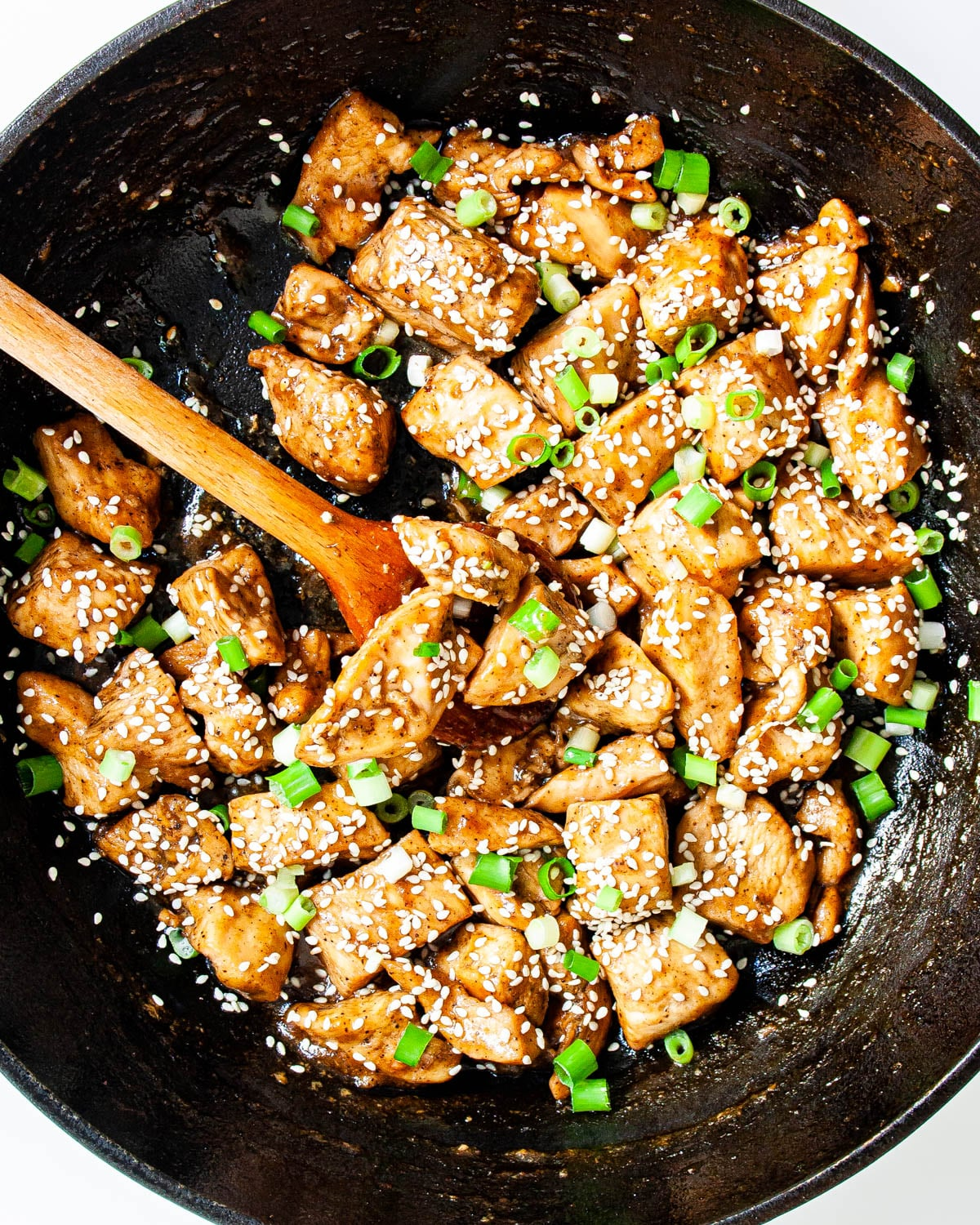 chicken teriyaki in a skillet garnished with sesame seeds and green onions