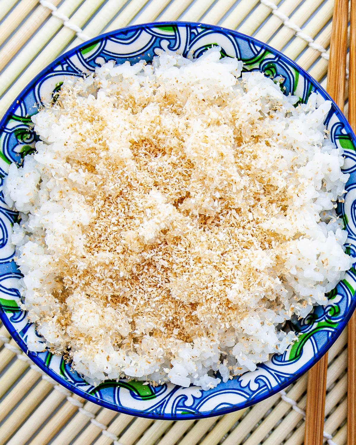 overhead shot of coconut rice in a bowl garnished with toasted coconut