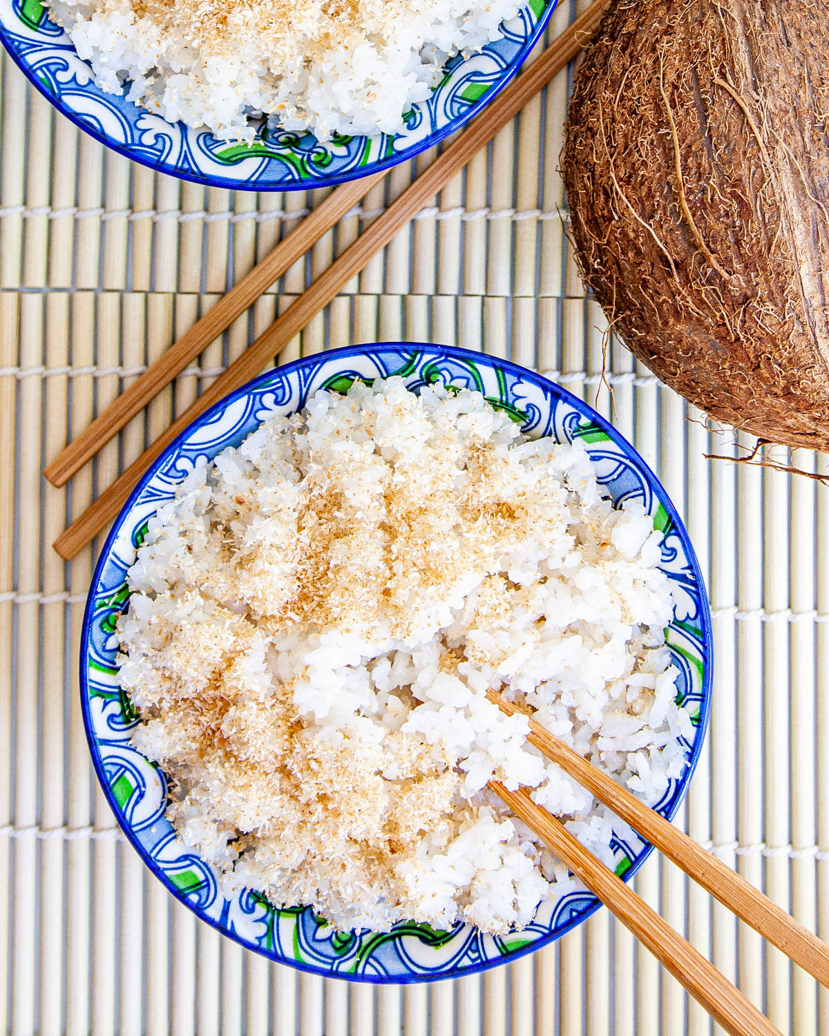 overhead shot of two bowls loaded with coconut rice next to a coconut