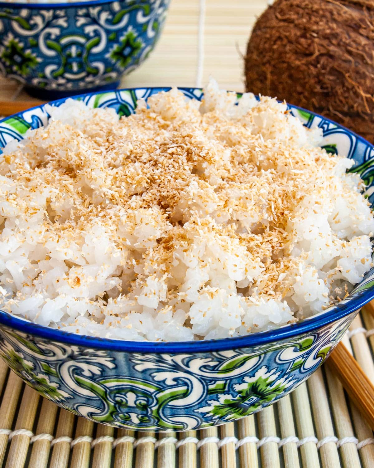 coconut rice in a blue bowl garnished with toasted coconut
