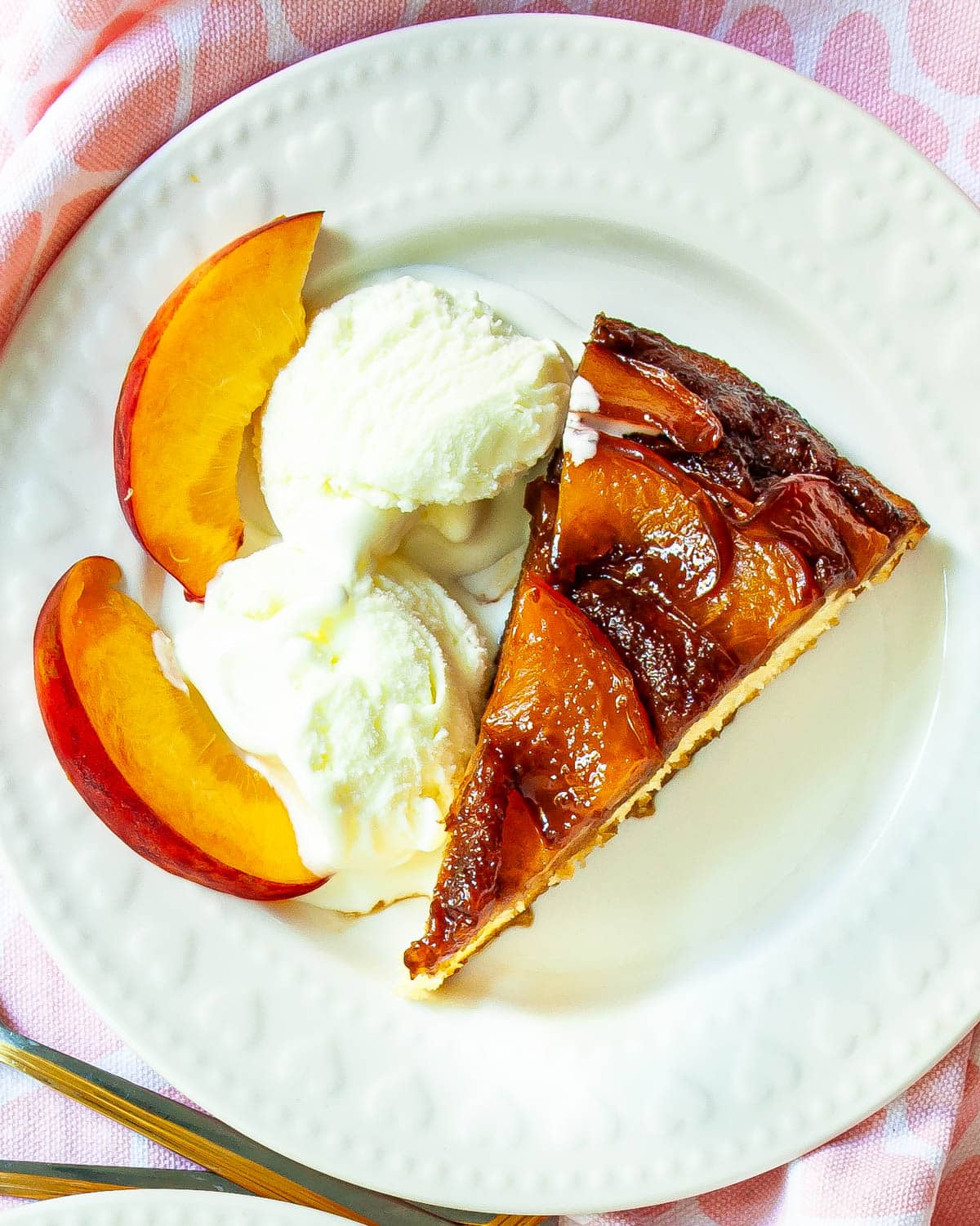a slice of Peach Upside Down Cake with 2 scoops of ice cream on a white plate