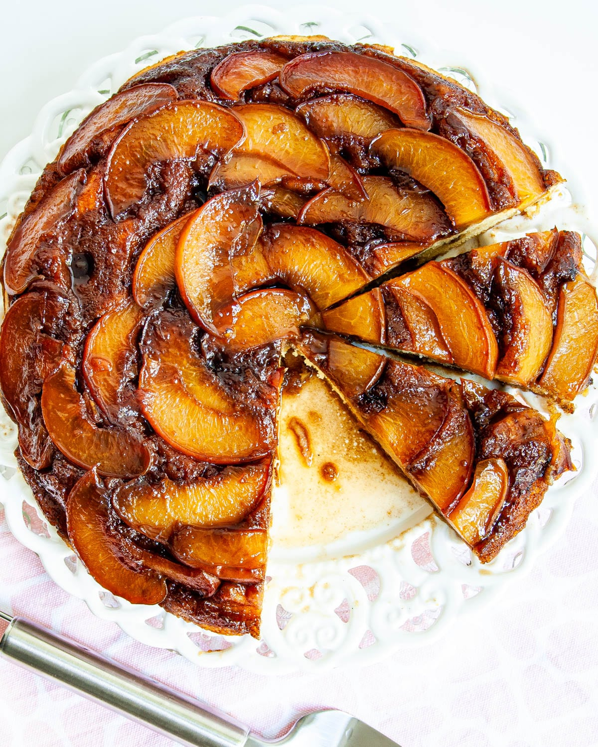 overhead shot of Peach Upside Down Cake on a white plate cut into slices
