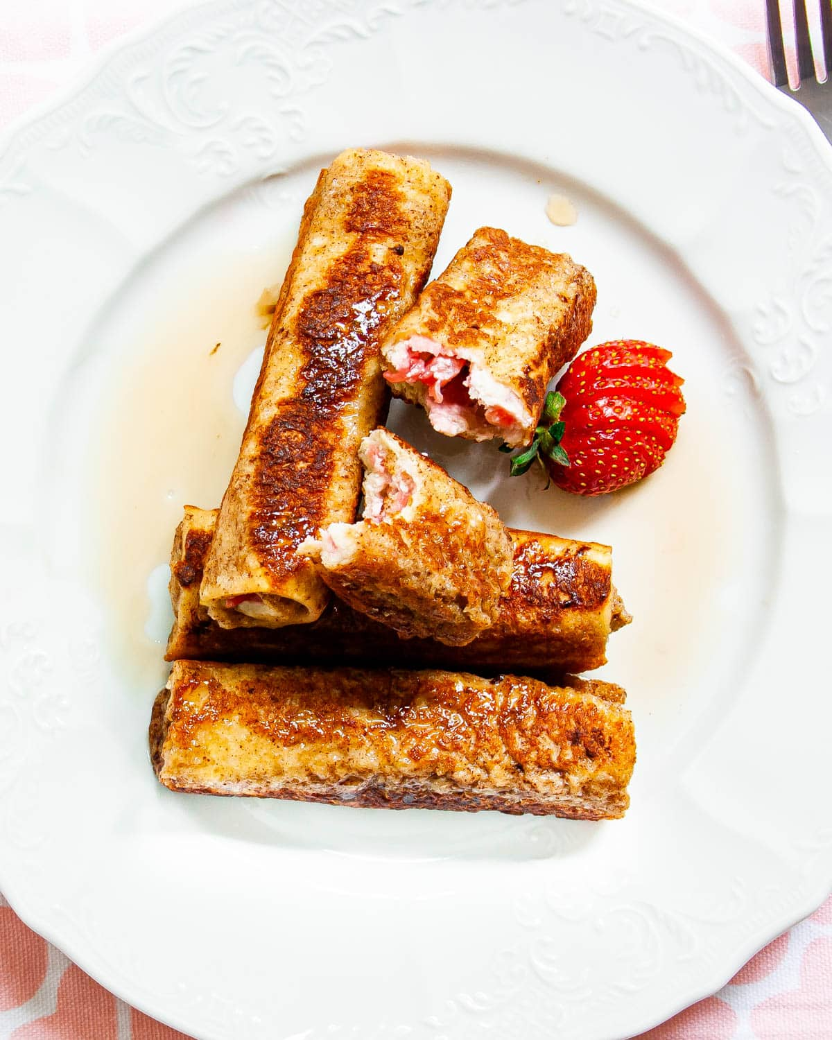 overhead shot of Strawberry Cream Cheese French Toast Roll Ups in a white plate and drizzled with maple syrup