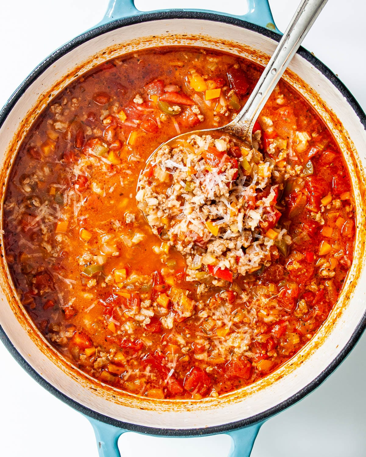 stuffed pepper soup in a large dutch oven with a ladle full of soup over it