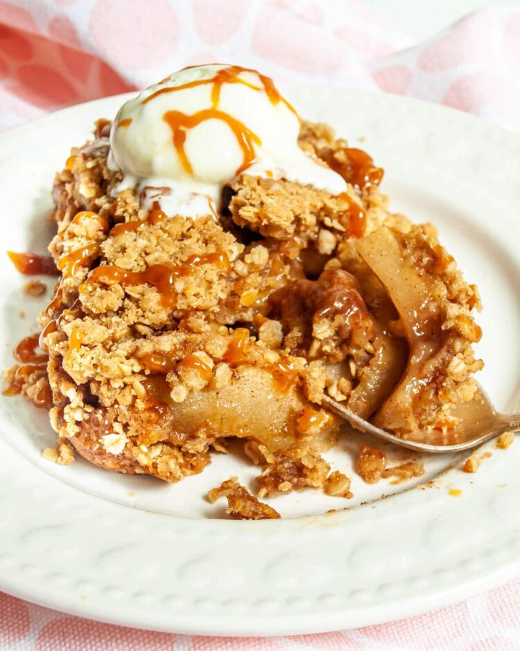 a slice of apple crisp on a plate with ice cream and caramel sauce