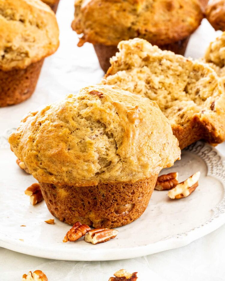 banana nut muffins on a plate with few pecans