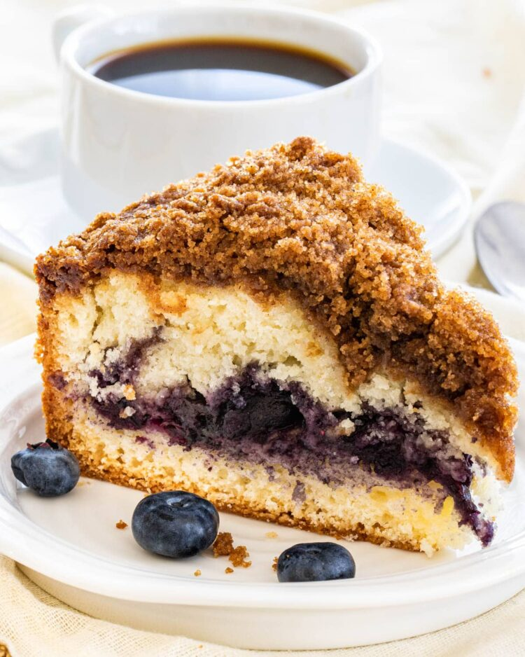 a slice of blueberry coffee cake on a white plate with a cup of coffee in the background