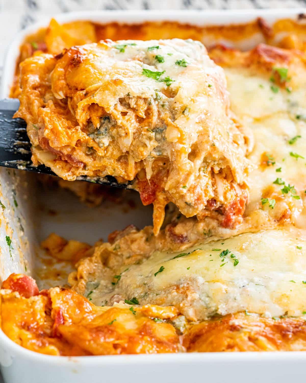 a spatula pulling a slice of lasagna from a casserole dish