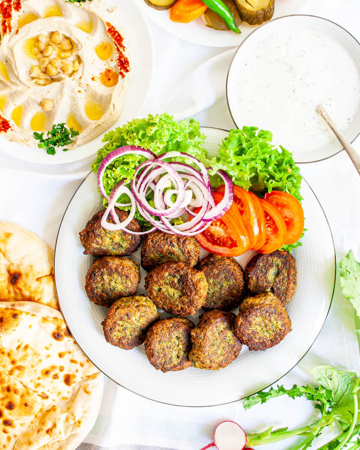 falafel on a white plate with tomato slices, onions and lettuce