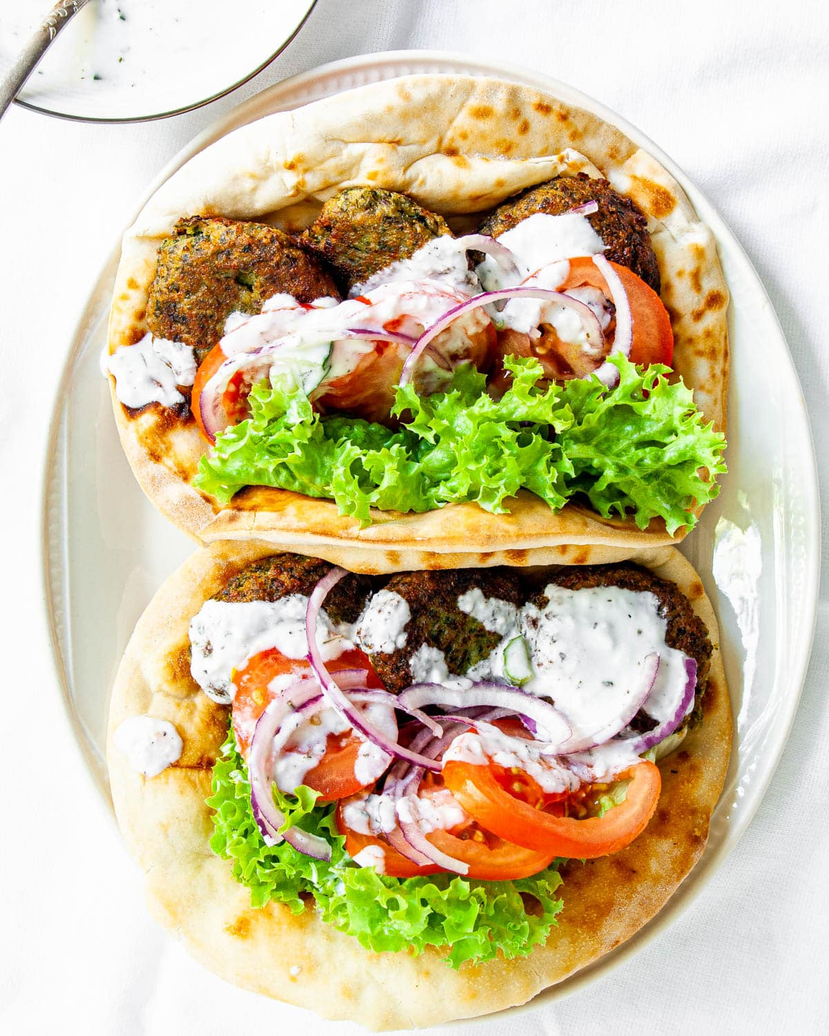 two falafel stuffed pittas on a white plate