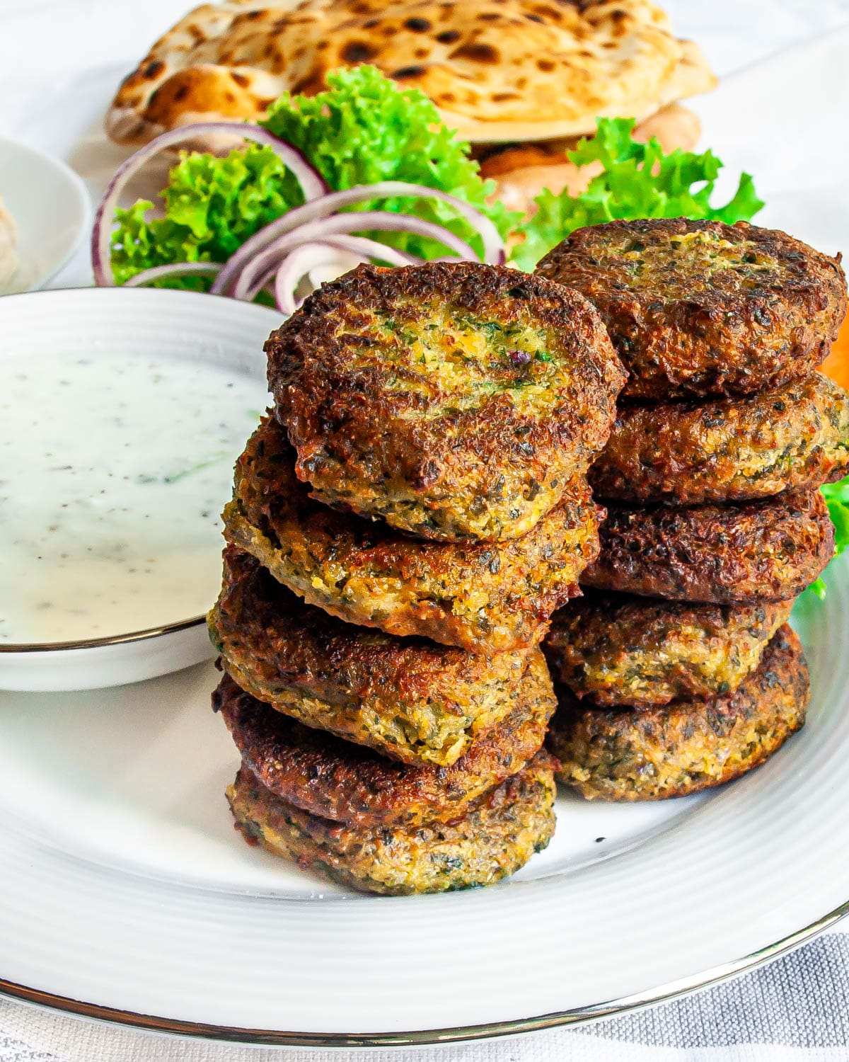two stacks of falafel with tzatziki sauce in the background