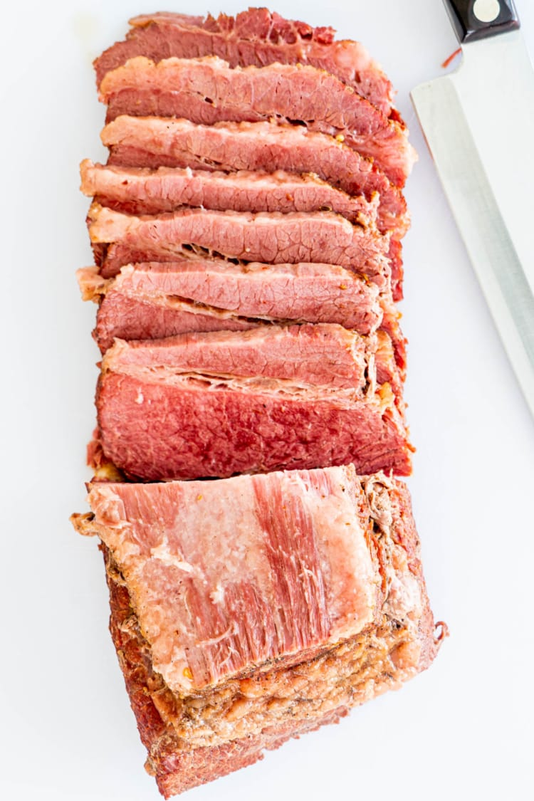 overhead shot of corned beef sliced up on a white cutting board