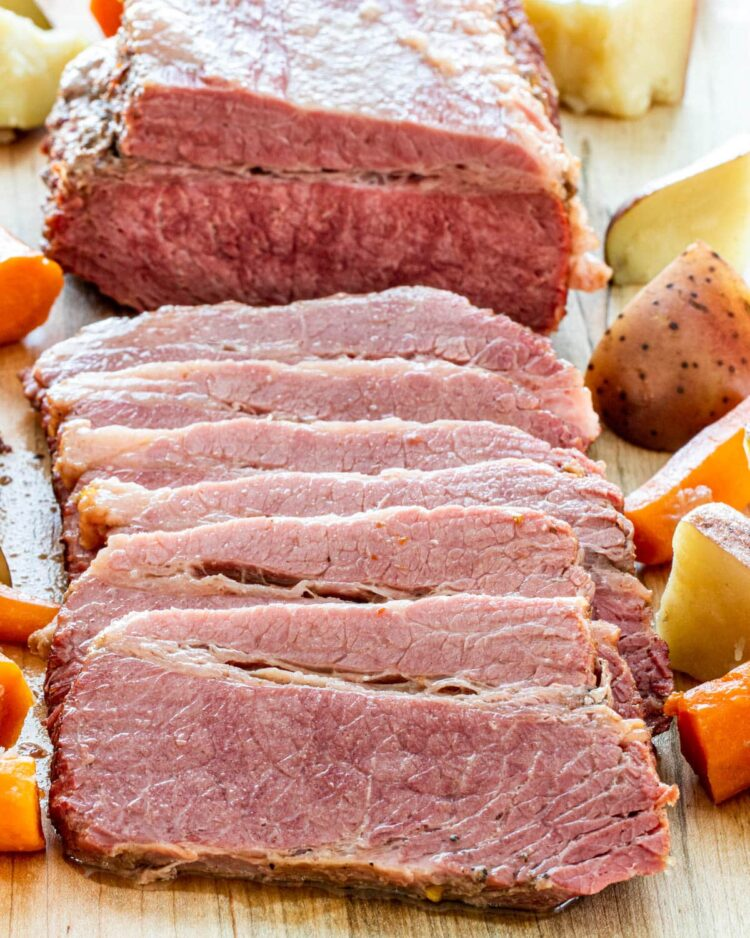 corned beef on a cutting board surrounded by potatoes and carrots