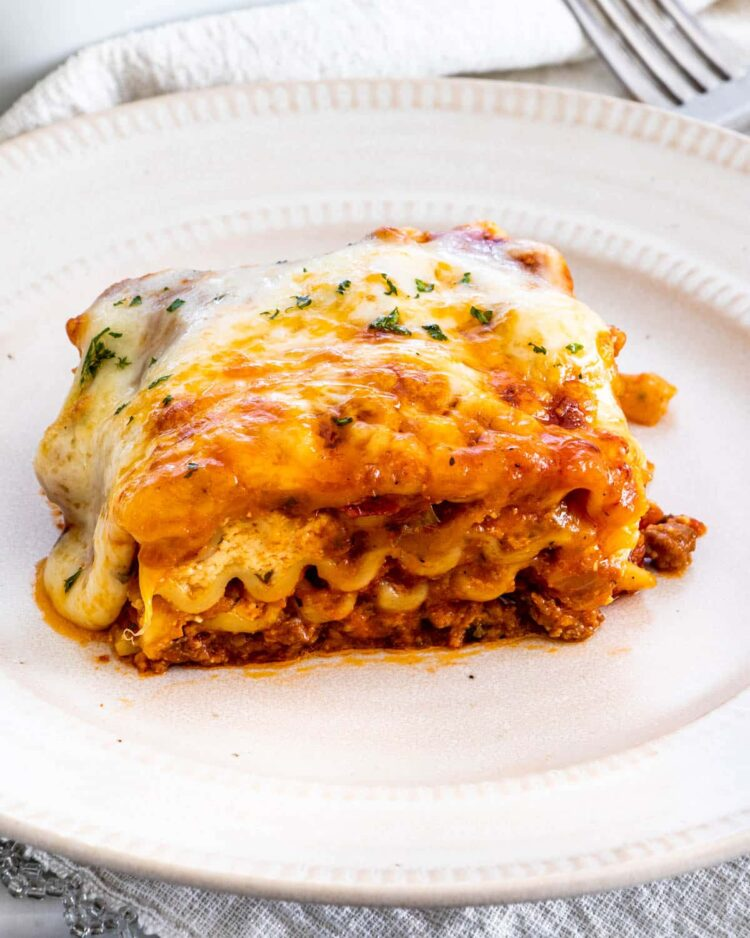 a slice of lasagna on a beige plate