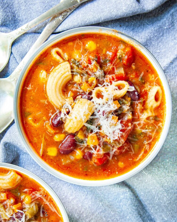 overhead shot of minestrone soup in a bowl topped with a bit parmesan cheese