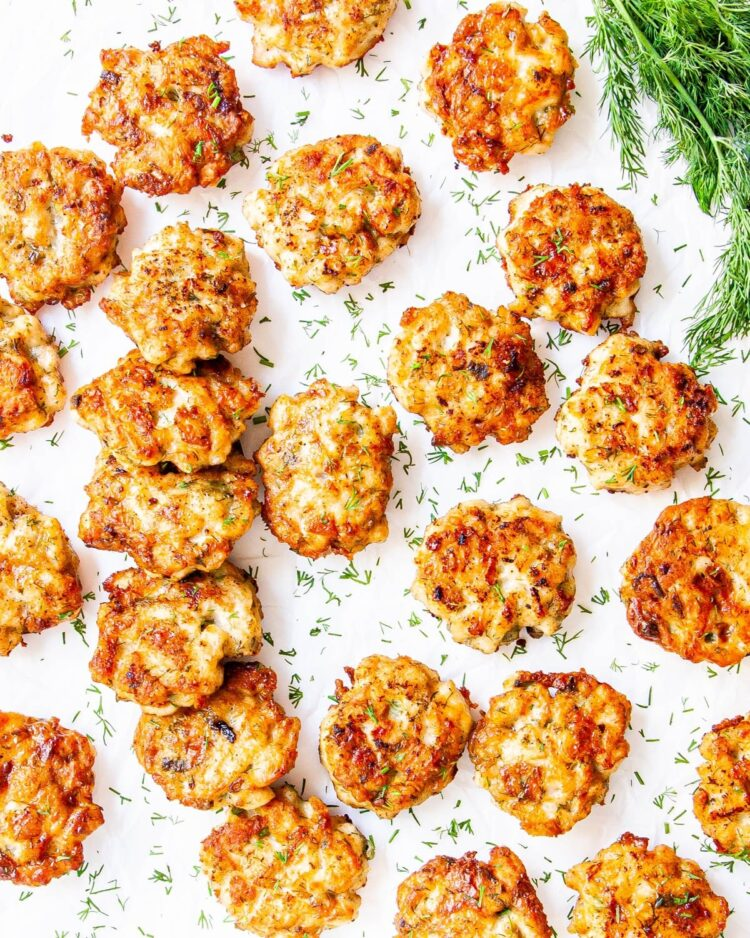 overhead shot of cheesy chicken fritters garnished with fresh dill