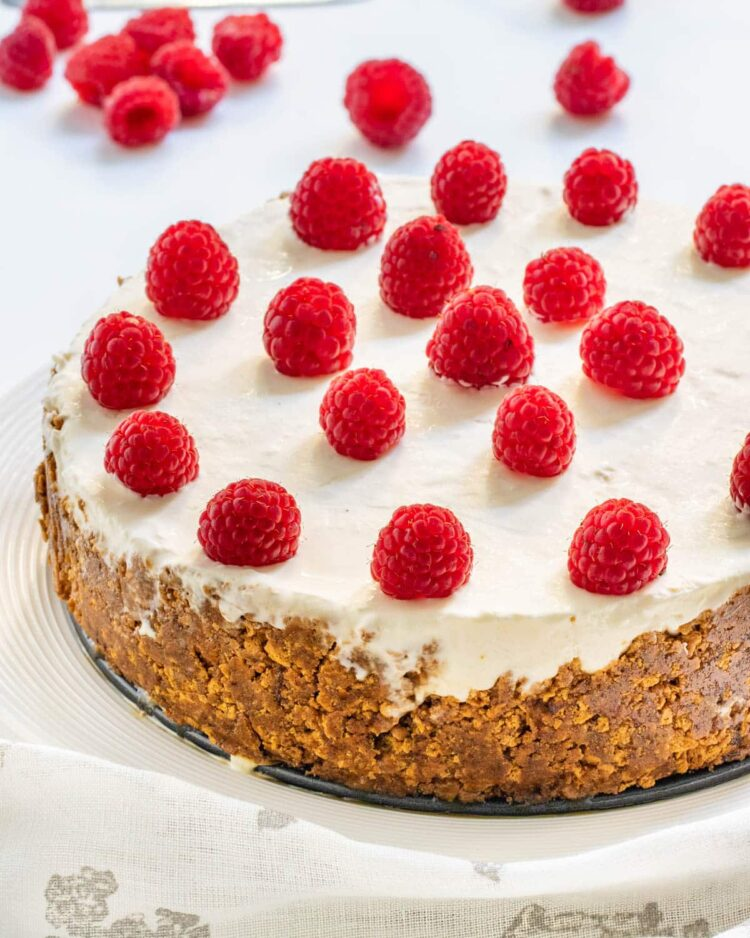 no bake cheesecake on a serving platter topped with raspberries