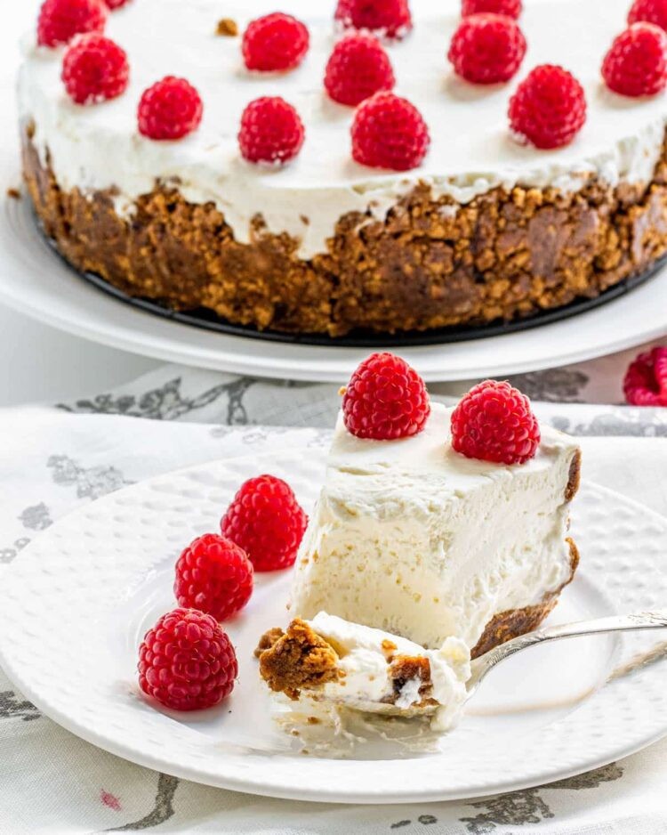 a slice of no bake cheesecake with a bite on a fork on a white plate topped with raspberries
